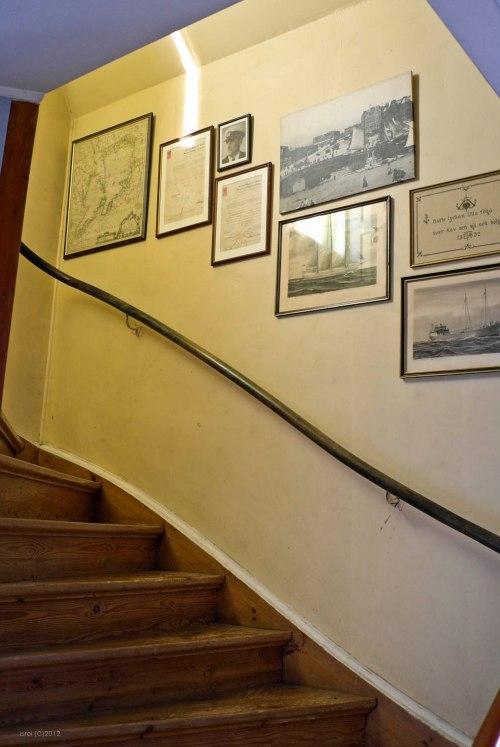 Tangga ke lantai dua yang penuh dengan peta dan foto tua